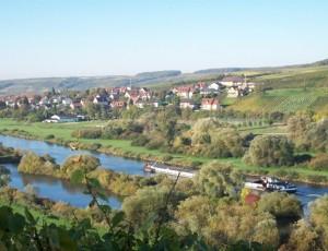 Obereisenheim in Franken, das direkt ans Mainufer reicht. Über den Ort zieht sich die Lage Höll bis nach Untereisenheim, die mit Muschelkalkböden nach Südosten Richtung Main abfällt und als sehr gute gelten darf.