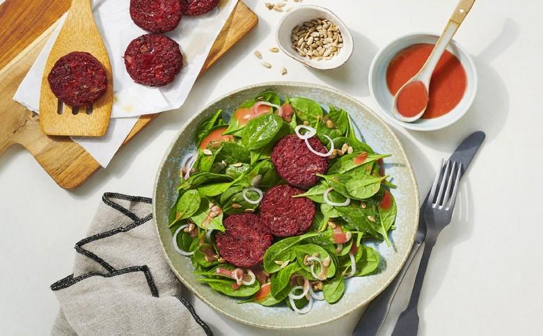 Leckeres Veggie-Rezept: Rote-Frühlingszwiebel-Taler auf Spinatsalat prima dazu ein feinherber Wein. Rezept: Deli-Reform; Foto: Stefan Schulte-Ladbeck